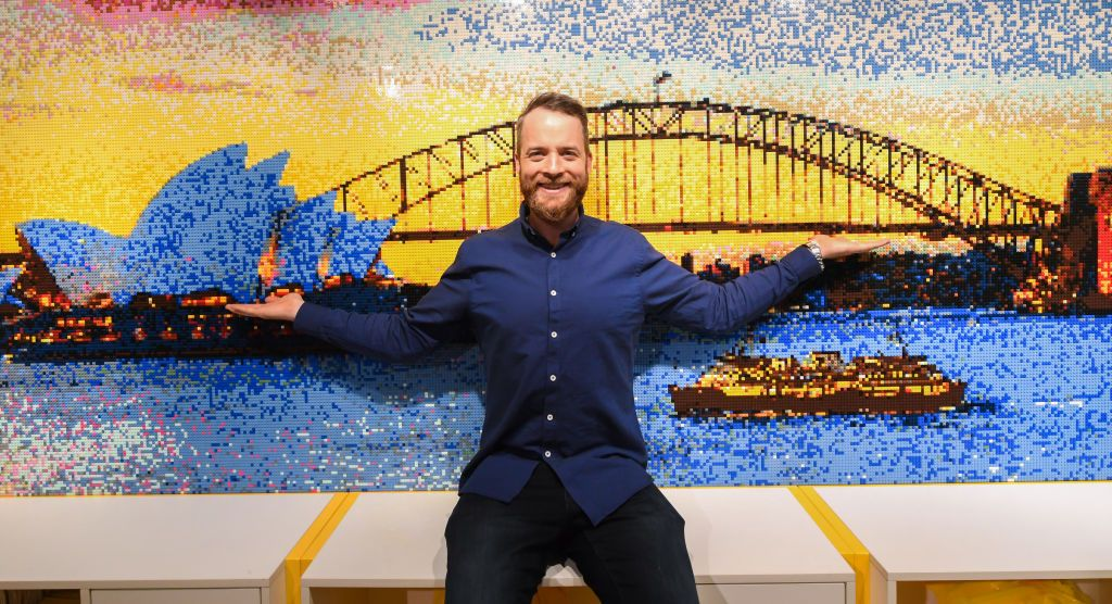 A man posing with his lego artwork of the Sydney Opera House