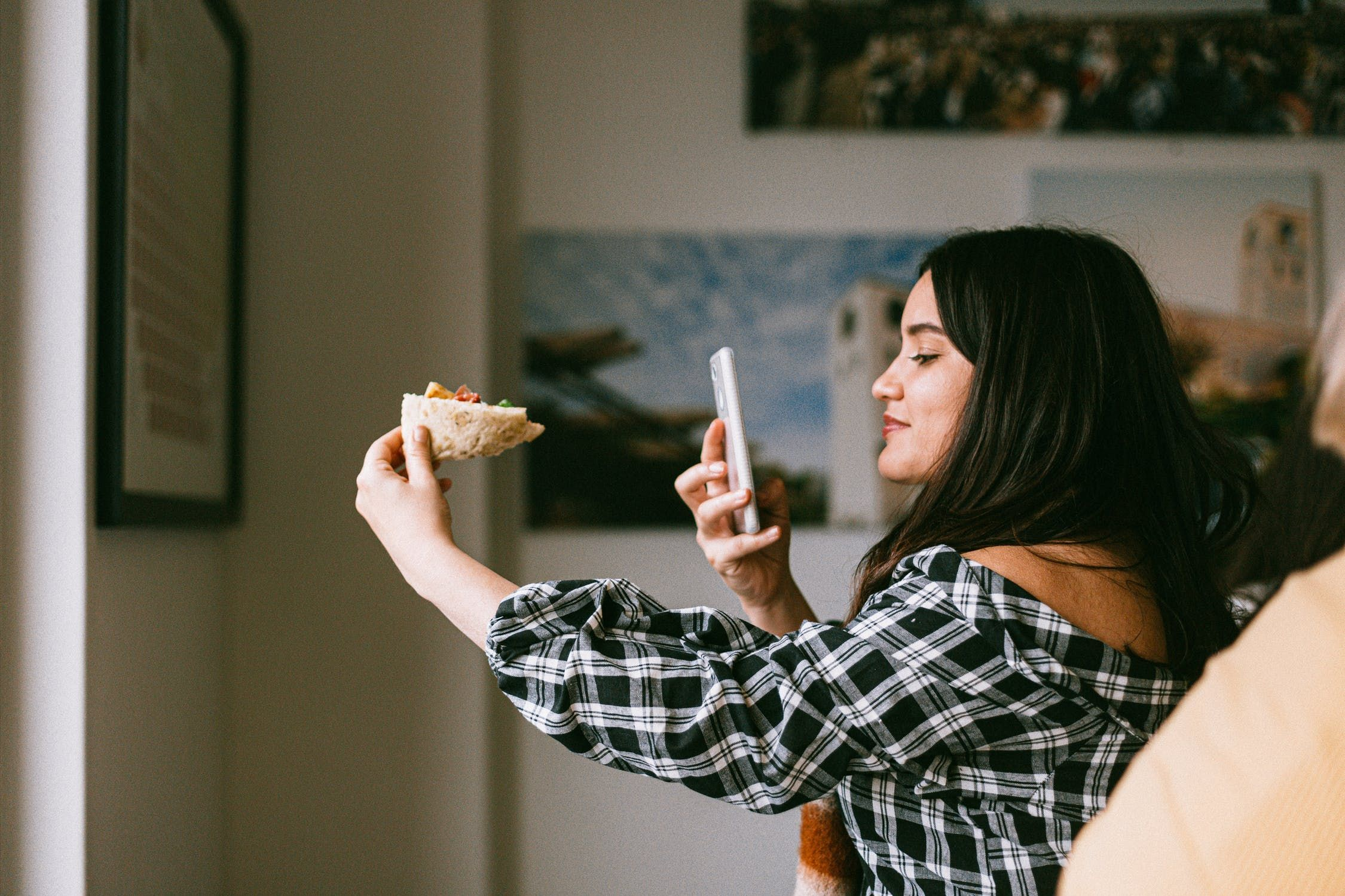 A girl taking a selfie of herself eating a sandwich