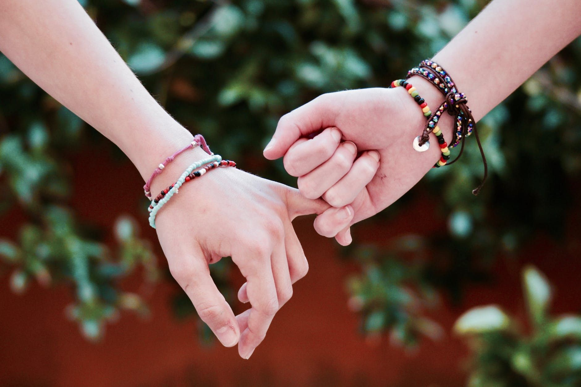Friends holding hands as they wear their friendship bracelets