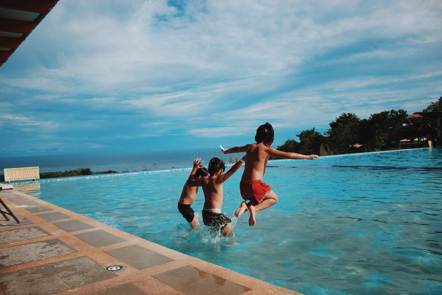 Three boys jumping into the pool