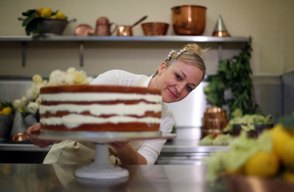 The baker who made Harry and Meghans wedding cake standing proudly in front of her work