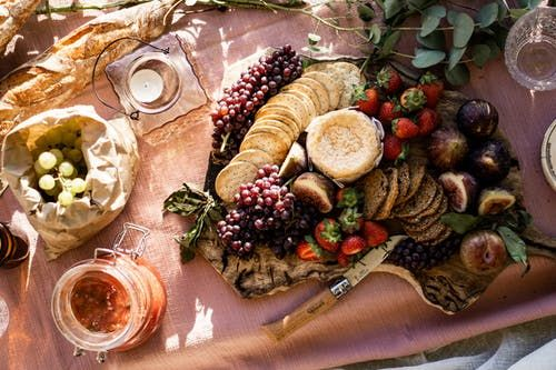 A luxurious picnic spread of cheeses and fruits