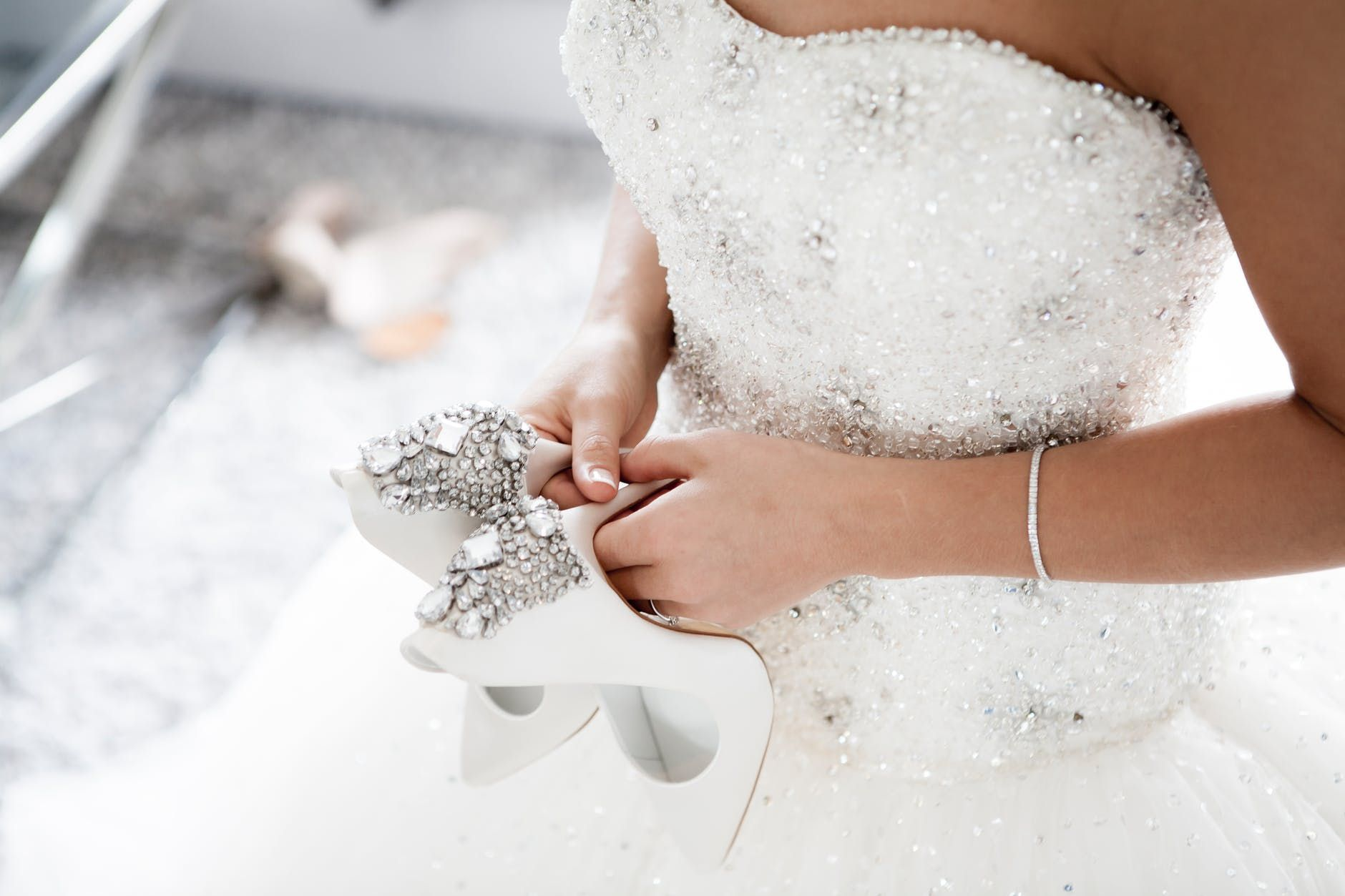 A bride in her wedding dress holding her shoes