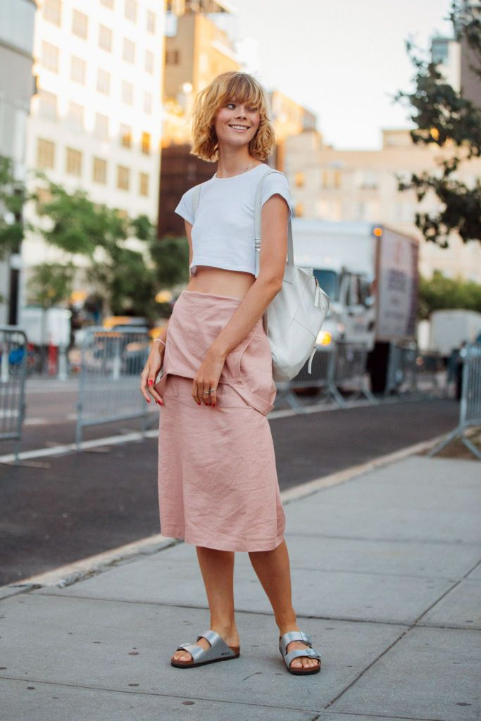 Model Irina Kravchenko wears a cropped white top, white backpack, skirt dress, silver Birkenstocks during New York Fashion Week
