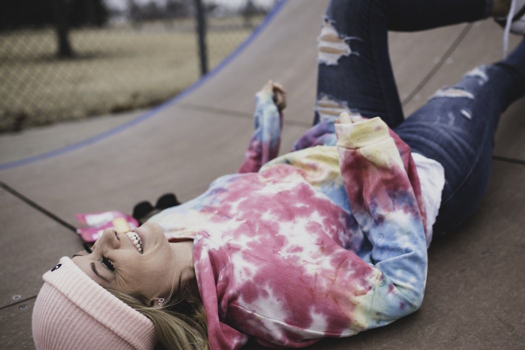 Girl in pink beanie hat and tie dye sweatshirt laying and laughing on a skating park ramp
