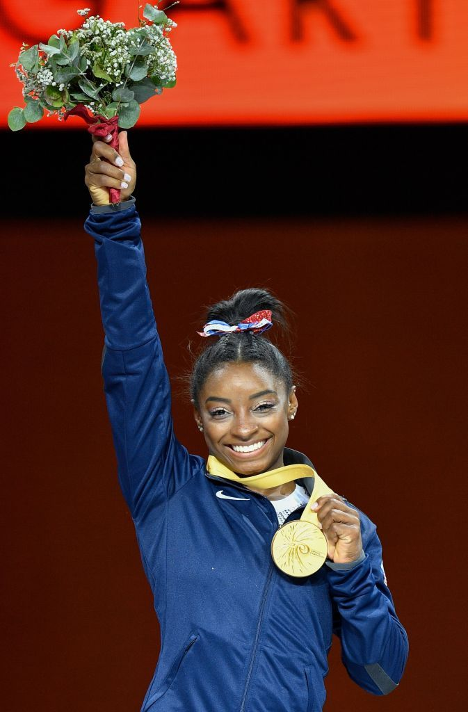 USA's Simone Biles poses on the podium during the medals ceremony of the womens all-around final at the FIG Artistic Gymnastics World Championships