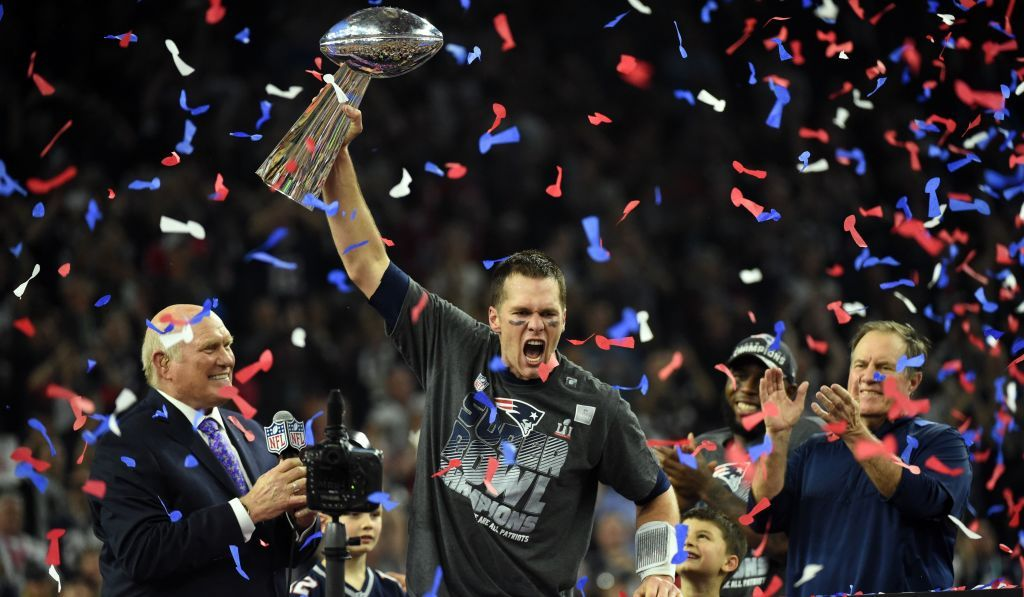 Tom Brady #12 of the New England Patriots holds the Vince Lombardi Trophy as Head coach Bill Belichick (R) looks on after defeating the Atlanta Falcons