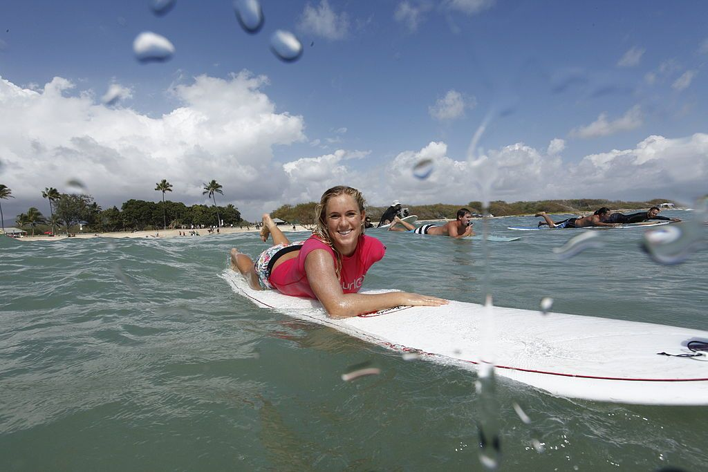 US surfer Bethan Hamilton paddling out on a surf board in a bright pink shirt