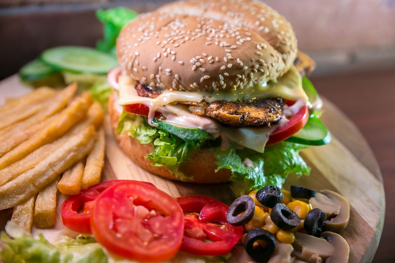 Sesame seed bun sandwich with chicken, lettuce, mayo, tomato, olives, corn, and french fries
