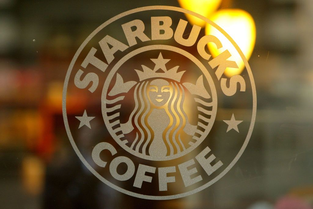 A logo is seen on the glass storefront door of a Starbucks coffee shop