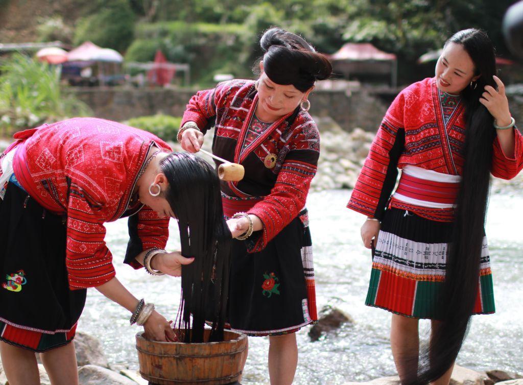 Women wash their long hair along the riverside in Huangluo Village of the Yao ethnic group in Longji Township of Longsheng County in July  2019