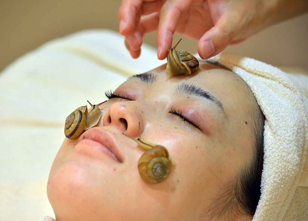 """Snails crawling on a woman's face as part of a new beauty treatment at """"Ci:z.Labo"""" Salon in Tokyo"""