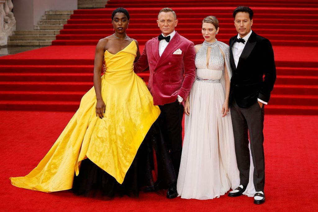 """English actor Lashana Lynch (L), English actor Daniel Craig (C) and French actor Lea Seydoux (2R) and US film director Cary Joji Fukunaga pose on the red carpet of the World Premiere of the James Bond 007 film """"No Time to Die"""" at the Royal Albert Hall in west London September 2021"""