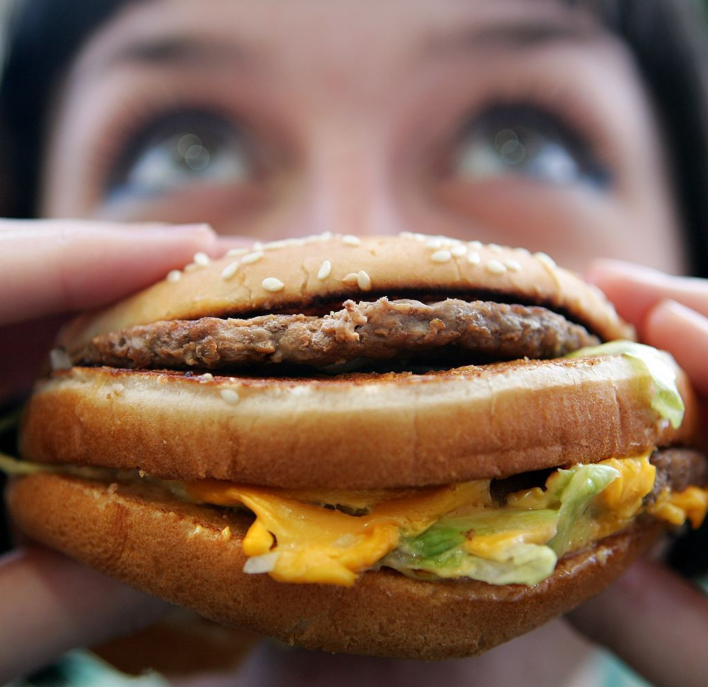 woman eating a cheeseburger in July 2007 in England